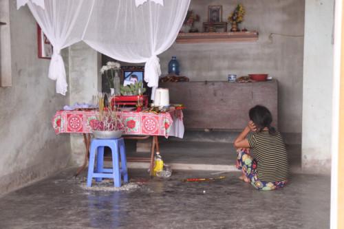 Người mẹ nghèo ngồi bất động trước di ảnh con là em Nguyễn Gia Tiến (HS Trường THPT Nguyễn Cảnh Chân).